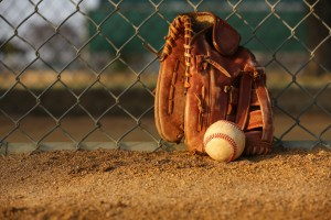 Baseball and Glove against the Fence